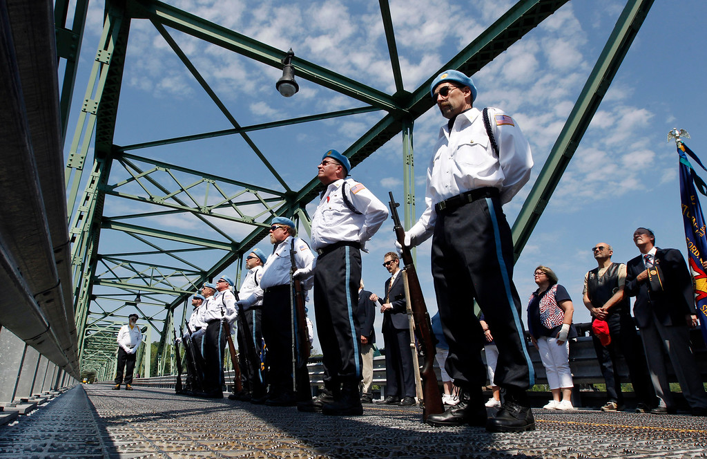. An Honor Guard stands on the Uhlerstown-Frenchtown Bridge over the Delaware River, between Uhlerstown, Pa. and Frenchtown, N.J., during Memorial Day ceremonies Monday, May 25, 2015, in Frenchtown, N.J. (AP Photo/Mel Evans)