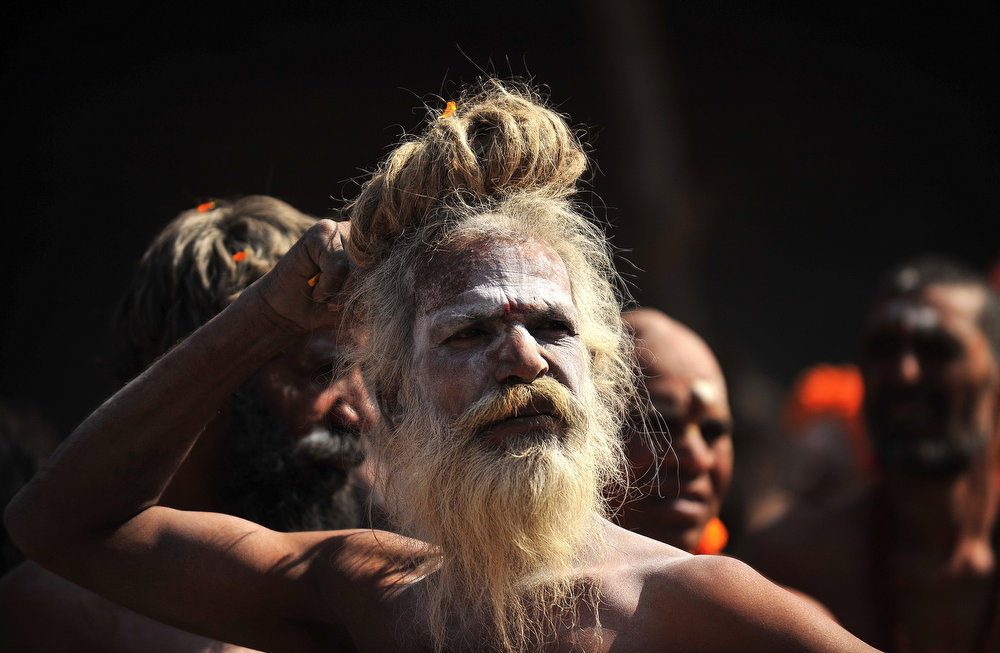 . Naga sadhus - Hindu holy men - take out a religious procession to offer holy water from the Ganga river at the Kashi Vishwanath Temple in Varanasi on March 10, 2013 on the occasion of Maha Shivaratri and the last day of the Kumbh. The festival of Maha Shivaratri is marked by Hindus through fasting and offering prayers in a night long vigil.   AFP PHOTO/ SANJAY KANOJIA