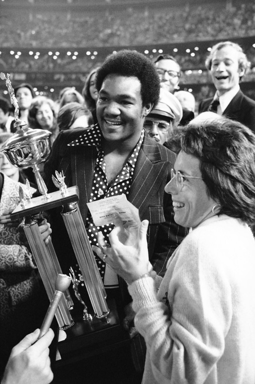 . Heavyweight Champion George Foreman presents the winner?s trophy and a check for $100,000 to Billie Jean King after she defeated Bobby Riggs in the winner-take-all tennis match at the Astrodome in Houston, Texas on Thursday, Sept. 21, 1973. Ms. King downed Riggs, 6-4; 6-3; 6-3. (AP Photo)