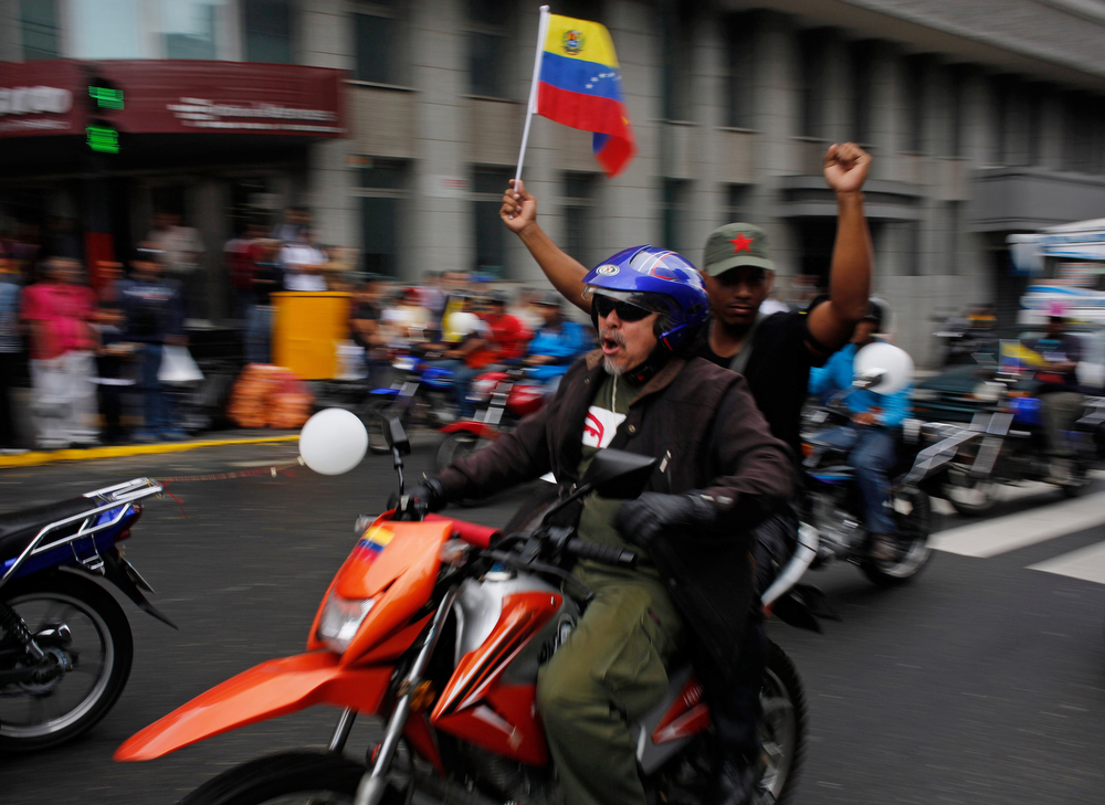 . Motorcyclists waving a Venezuelan flag attend a rally in support of Venezuela\'s President Nicolas Maduro in Caracas, Venezuela, Monday, Feb. 24, 2014. The pro-government rally comes at a time when Maduro\'s opponents have been staging countrywide protests for almost two weeks against the high crime rate and shortages of basic goods. Maduro has called for a national peace conference this week to address the unrest. (AP Photo/Rodrigo Abd)