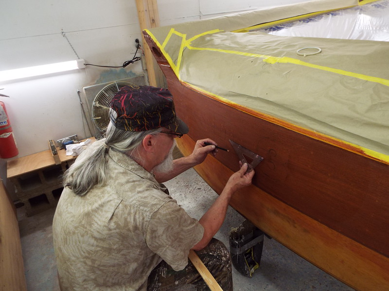 Sign painter starting to lay out the transom logo.