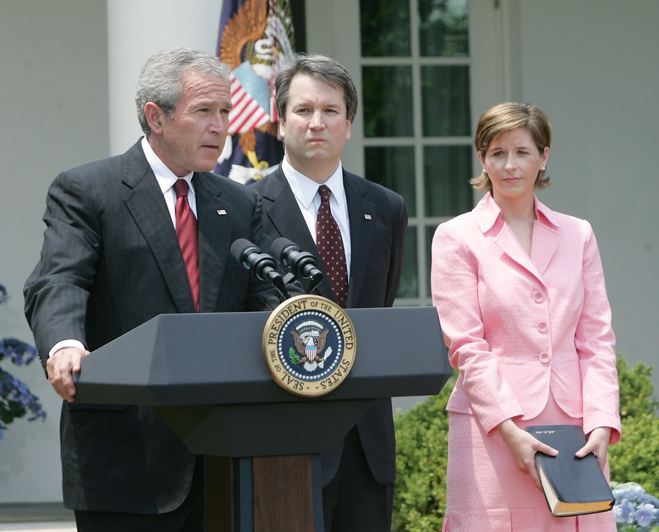 . President Bush, speaks in the Rose Garden of the White House before the swearing-in of Brett Kavanaugh, center, as Judge for the U.S. Court of Appeals for the District of Columbia Thursday, June 1, 2006 in Washington. Holding the Bible is Kavanaugh\'s wife Ashely Kavanaugh. (AP Photo/Pablo Martinez Monsivais)