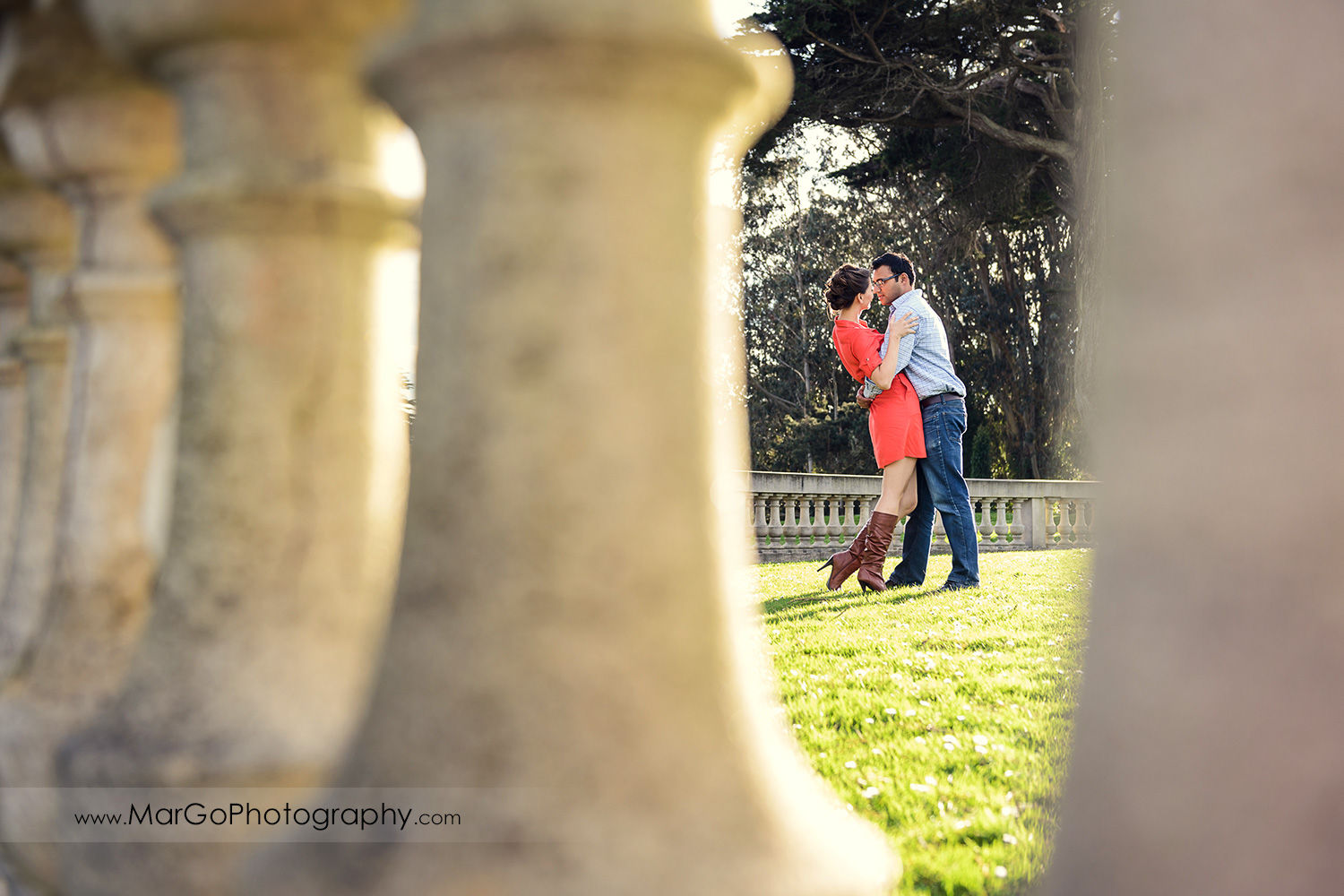 man in blue shirt and woman in red dress dancing during engagement session at San Francisco Legion of Honor shot through the columns