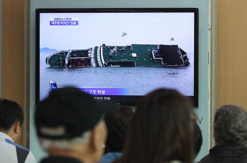 . People watch a TV news program showing a sinking passenger ship, at Seoul Railway Station in Seoul, South Korea, Wednesday, April 16, 2014. The South Korean passenger ship carrying more than 470 people, including many high school students, is sinking off the country\'s southern coast Wednesday after sending a distress call, officials said. There are no immediate reports of causalities.(AP Photo/Ahn Young-joon)