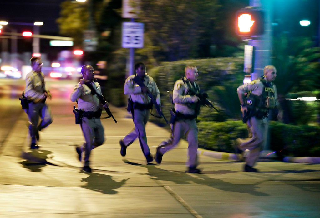 . Police run to cover at the scene of a shooting near the Mandalay Bay resort and casino on the Las Vegas Strip, Sunday, Oct. 1, 2017, in Las Vegas. Multiple victims were being transported to hospitals after a shooting late Sunday at a music festival on the Las Vegas Strip. (AP Photo/John Locher)