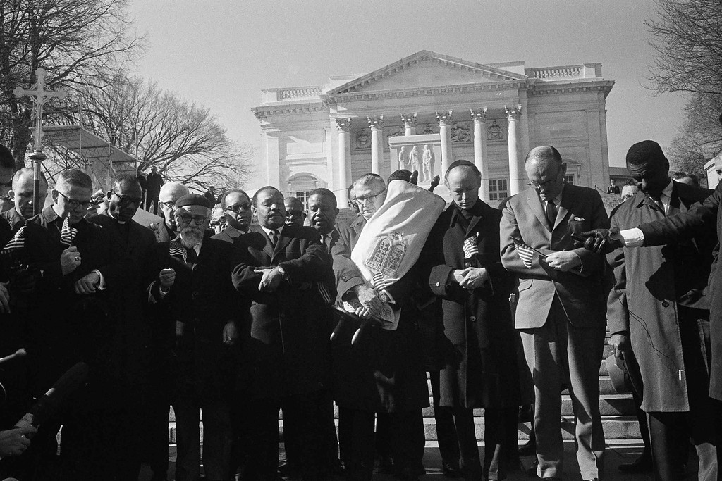 . Leaders in a Vietnam war protest stand in silent prayer in Arlington National Cemetery, Feb. 6, 1968. Front row, from left: Rev. Andrew Young, executive vice president of the Southern Christian Leadership Conference; Bishop James P. Shannon, Roman Catholic auxiliary bishop of Minneapolis and St. Paul; Rabbi Abraham Heschel, professor at the Jewish Theological Seminary, New York; the Rev. Dr. Martin Luther King Jr., and Rabbi Maurice Eisendrath, president of the Union of American Hebrew Congregations. The Tomb of the Unknown Soldier and Arlington Amphitheater are in background.  (AP Photo/Harvey Georges)