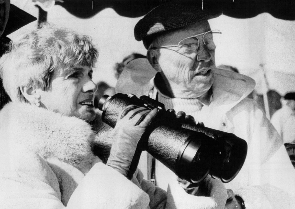 . The parents of teacher astronaut Christa McAuliffe, Edward and Grace Corrigan of Framingham, Mass., bundled up against the chilly windy weather at the VIP area at Kennedy Space Center look out towards launch pad 39b through high powered binoculars. McAuliffe perished in the Challenger explosion along with the other 6 crew members aboard the flight. Denver Post Library Archive