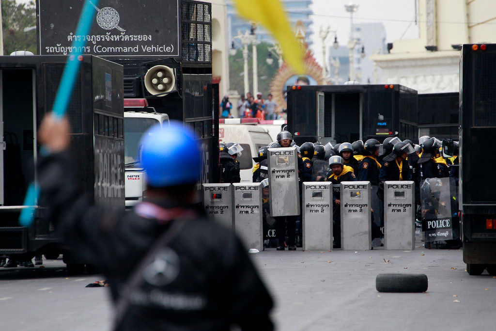 . A Thai protester confronts with police officers prior to a clash between police force and anti-government protesters near democracy monument, background, Tuesday, Feb. 18, 2014 in Bangkok, Thailand.  (AP Photo/Wason Wanichakorn)