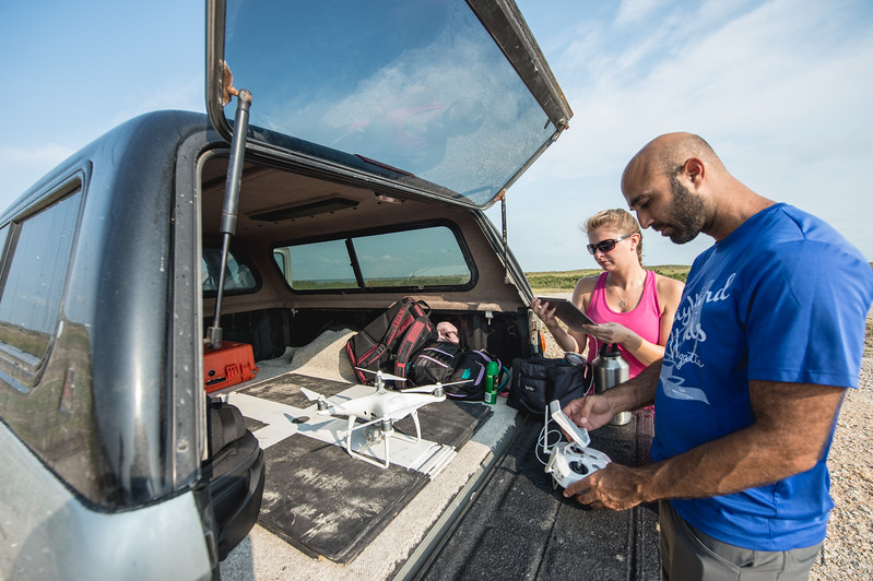 Melanie Gingrass (left) and Yeoshua Cohen initialize an Unmanned Air Vehicle as they prepare to take aerial photos of the marshes in Mustang Island.