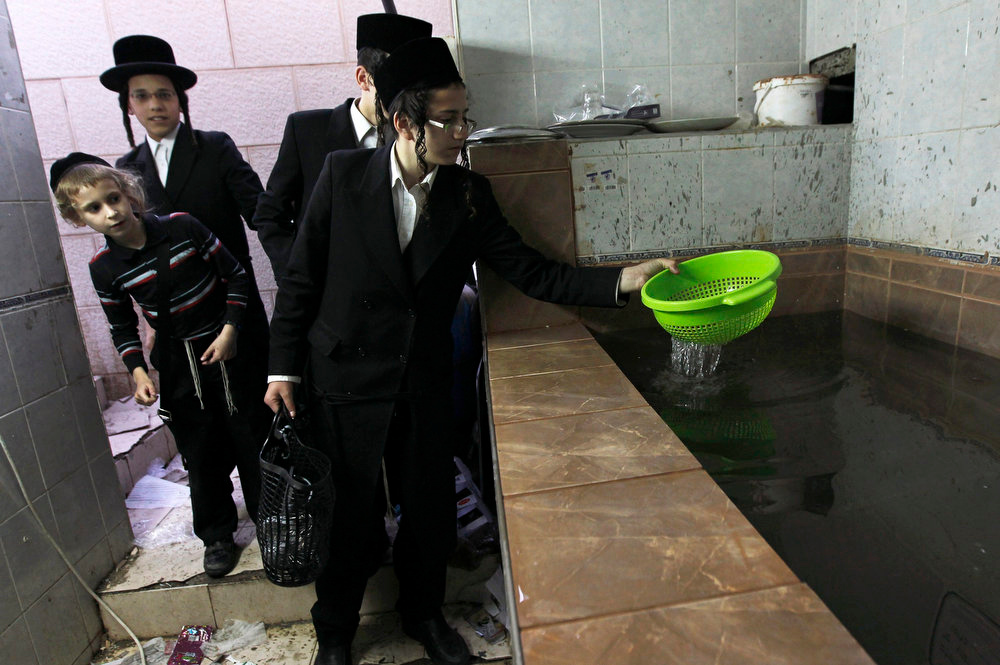 . An ultra-Orthodox Jewish youth dips a strainer in water to remove remains of leaven in preparation for the upcoming Jewish holiday of Passover in the southern city of Ashdod March 20, 2013. Passover, which starts next week, commemorates the flight of Jews from ancient Egypt, as described in the Exodus chapter of the Bible. According to the account, the Jews did not have time to prepare leavened bread before fleeing to the promised land. REUTERS/Amir Cohen
