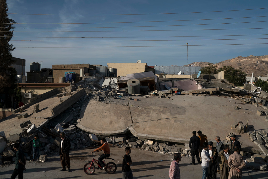 . People walk next to a destroyed house after an earthquake, in the city of Darbandikhan, northern Iraq, Monday, Nov. 13, 2017. A powerful 7.3 magnitude earthquake near the Iraq-Iran border has killed over 350 people across both countries, sent residents fleeing their homes into the night and was felt as far away as the Mediterranean coast. (AP Photo/Felipe Dana)