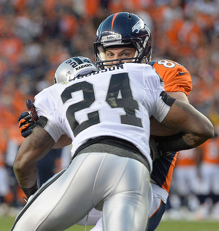. Denver Broncos wide receiver Wes Welker (83) gets hit by Oakland\'s Charles Woodson in the first quarter at Sports Authority Field at Mile High in Denver on Monday, September 23, 2013. The Broncos beat the Raiders, 37-21.   (Photo by John Leyba/The Denver Post)