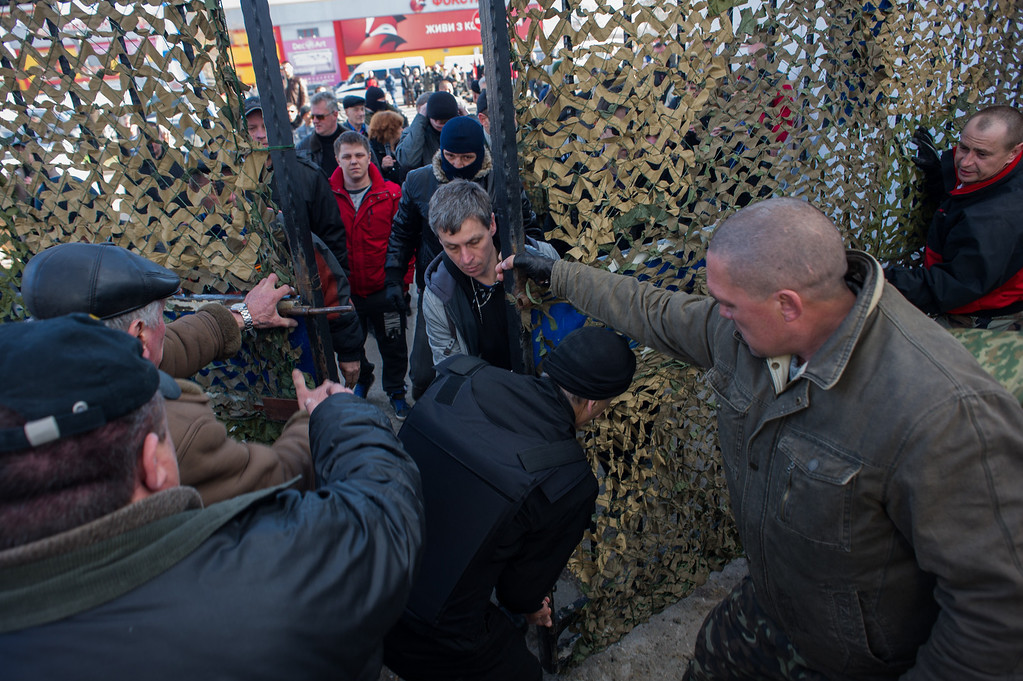 . Crimean pro-Russian self-defense forces open a gate to the territory of the Ukrainian navy headquarters in Sevastopol, Crimea, Wednesday, March 19, 2014. Crimea\'s self-defense forces on Wednesday stormed the Ukrainian navy headquarters in the Black Sea port of Sevastopol, taking possession without resistance a day after Russia signed a treaty with local authorities to annex the region.  (AP Photo/Andrew Lubimov)