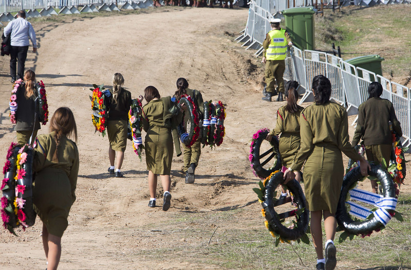 . Israeli soldiers carry wreaths of flowers for the burial ceremony of former Israeli prime minister Ariel Sharon\'s as his body arrives at the grave site where his second wife Lily is buried, on January 13, 2014 at the family ranch Havat Shikmin, near the Israeli city of Sderot in the southern Negev desert. (JACK GUEZJACK GUEZ/AFP/Getty Images)