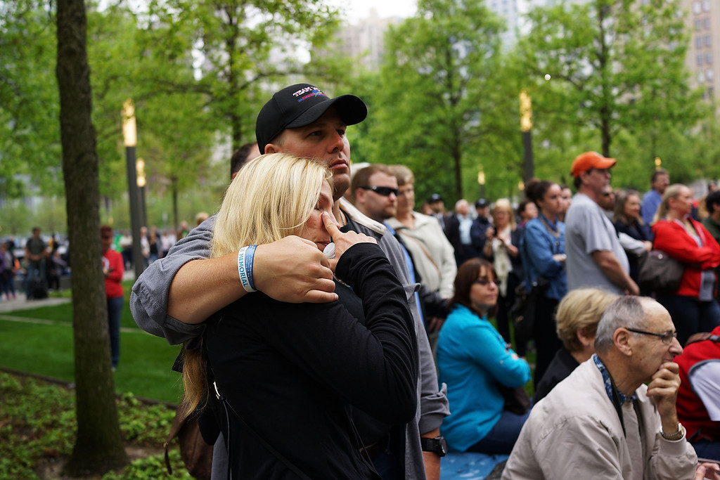 . People watch a live video from the Ground Zero memorial site of the dedication ceremony of the National September 11 Memorial Museum in New York on Thursday, May 15, 2014.  (AP Photo/Spencer Platt, Pool)