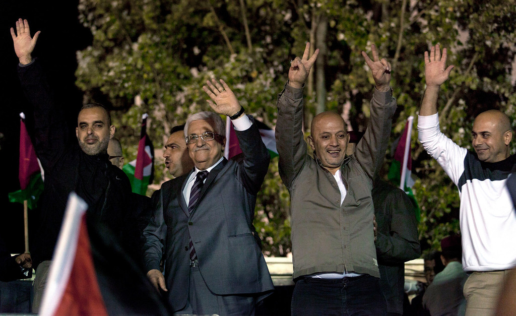 . Palestinian President Mahmoud Abbas, second left, and freed prisoners greet the crowd during a welcome ceremony at the Palestinian Authority headquarters, in the West Bank city of Ramallah, Wednesday, Oct. 30, 2013. Israel freed 26 Palestinian prisoners early Wednesday, the second of four batches to be released as part of a deal that set in motion the current Israeli-Palestinian peace talks. (AP Photo/Nasser Nasser)