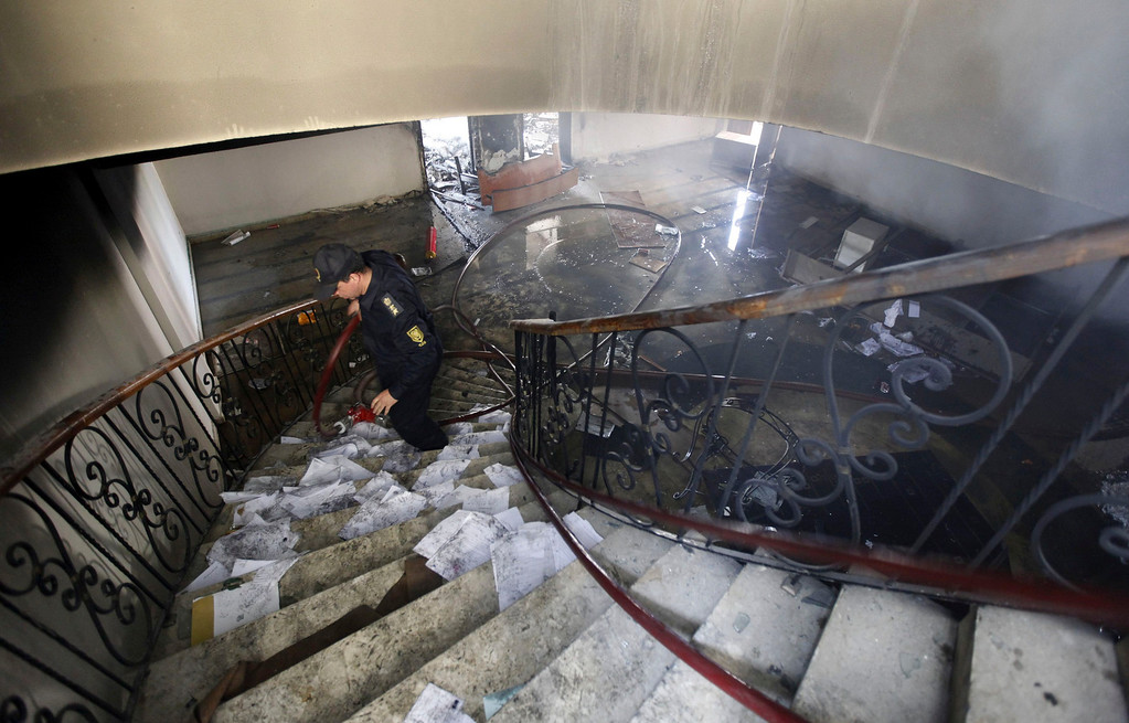 """. A firefighter walks up the stairs at the headquarters of the Egyptian Soccer Federation after Al Ahly fans, also known as \""""Ultras\"""" set it on fire following a court verdict, in Cairo March 9, 2013.  REUTERS/Amr Abdallah Dalsh"""