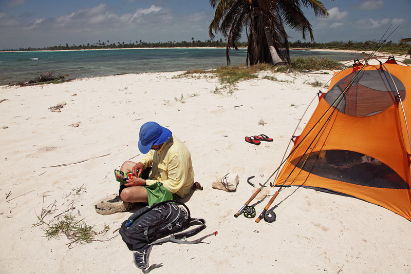 A fly fisherman searches for the perfect fly while camping on the Costa Maya Mexico