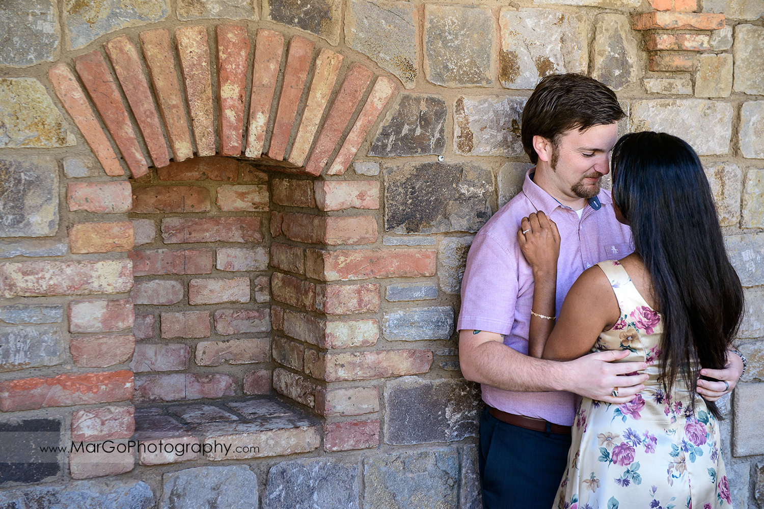 man in pink shirt and Indian woman in flower dress leaning against the brick wall and looking at each other during engagement session at Castello di Amorosa in Calistoga