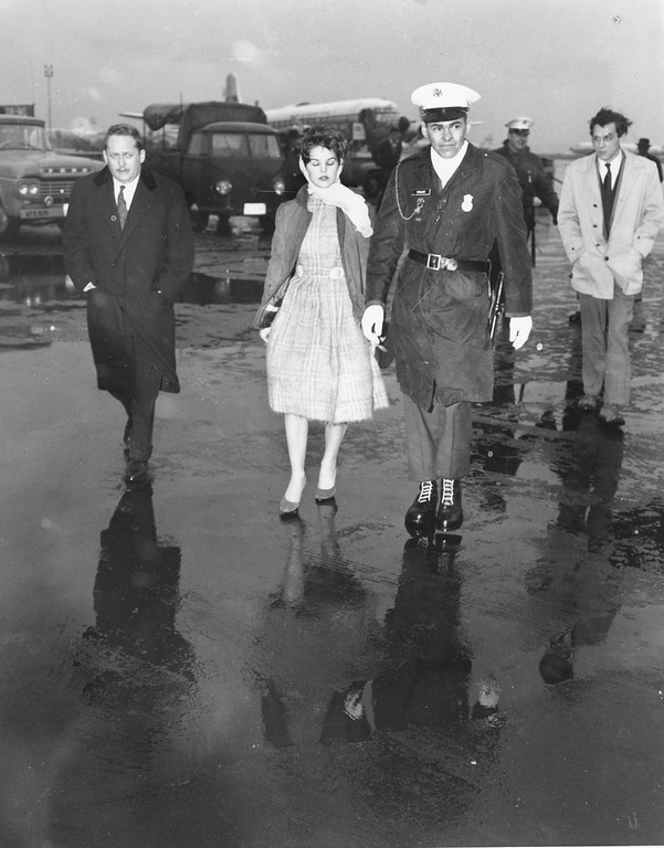 . A U.S. military policeman escorts Priscilla Beaulieu, 16, after she broke through a barrier trying to bid her boyfriend Elvis Presley goodbye at Rhine-Main airbase in Frankfurt/Main, Germany on March 2, 1960. (AP Photo)