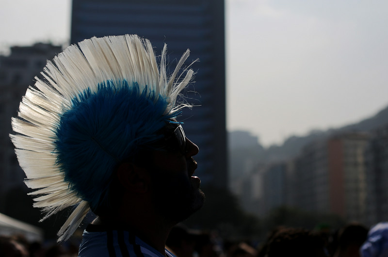 . An Argentina soccer fan, wearing a Mohawk-styled wig in his nation\'s flag colors, watches his team\'s World Cup round of 16 match against Switzerland on a live telecast inside the FIFA Fan Fest area on Copacabana beach in Rio de Janeiro, Brazil, Tuesday, July 1, 2014. (AP Photo/Leo Correa)