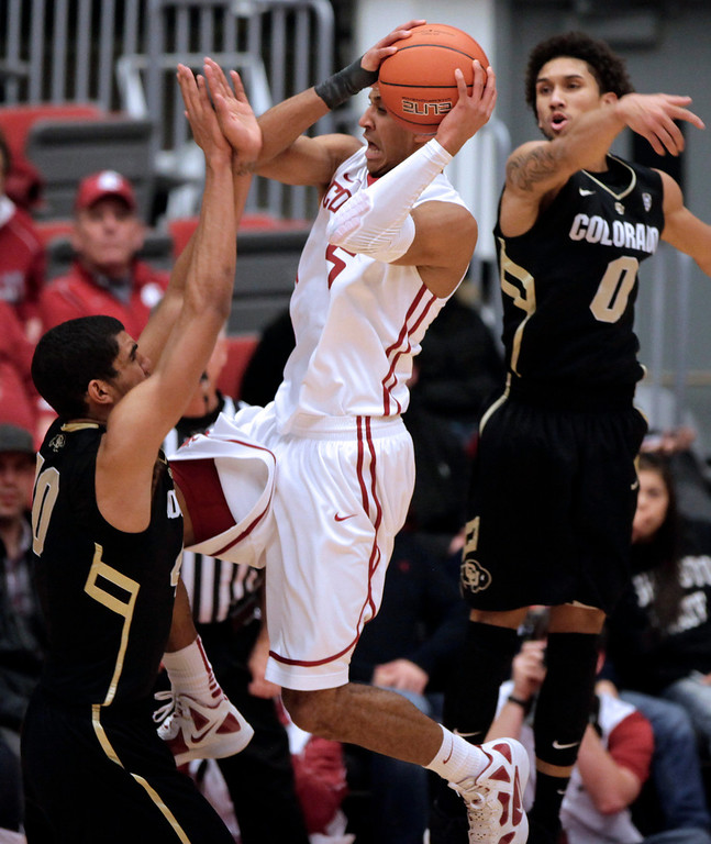 . Washington State guard Will DiIorio (5) drives against Colorado forward Josh Scott (40) after drawing a foul on guard Askia Booker (0) during the second half of an NCAA college basketball game Saturday, Jan. 19, 2013, in Pullman, Wash. Colorado won 58-49. (AP Photo/Dean Hare)