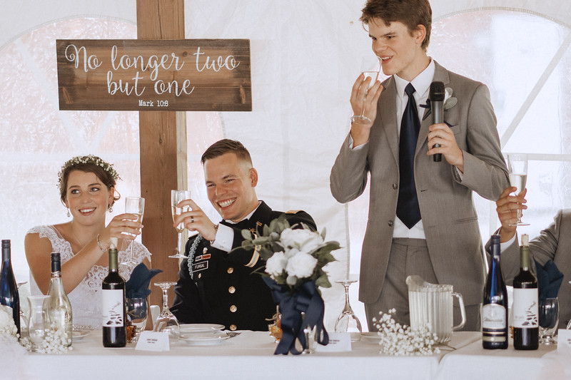 Bride and groom grin as they toast champagne flutes.