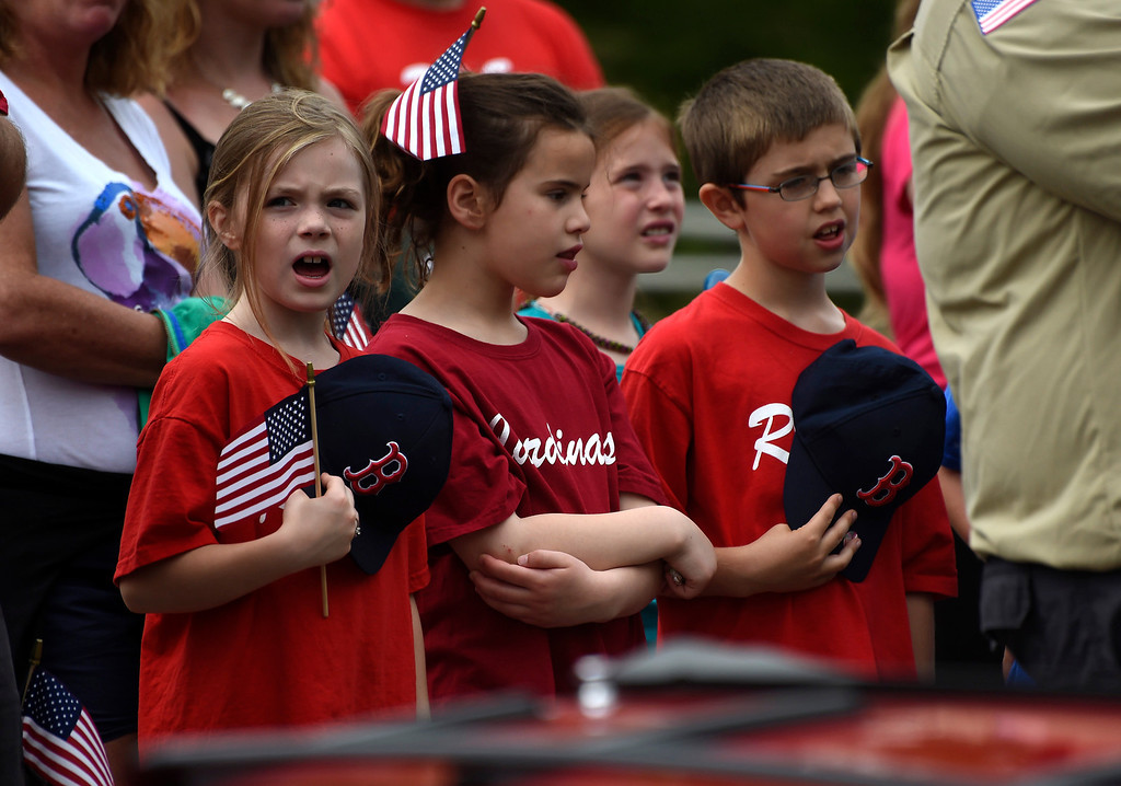 . Kayla Rice/Reformer (L-R) Ashlyn Honeycutt, Adeline Nardolillo and Brayden Eastman, all 8 years old, sing along during the National Anthem after walking with their Coach Pitch baseball teams in the Hinsdale Memorial Day parade on Monday morning.