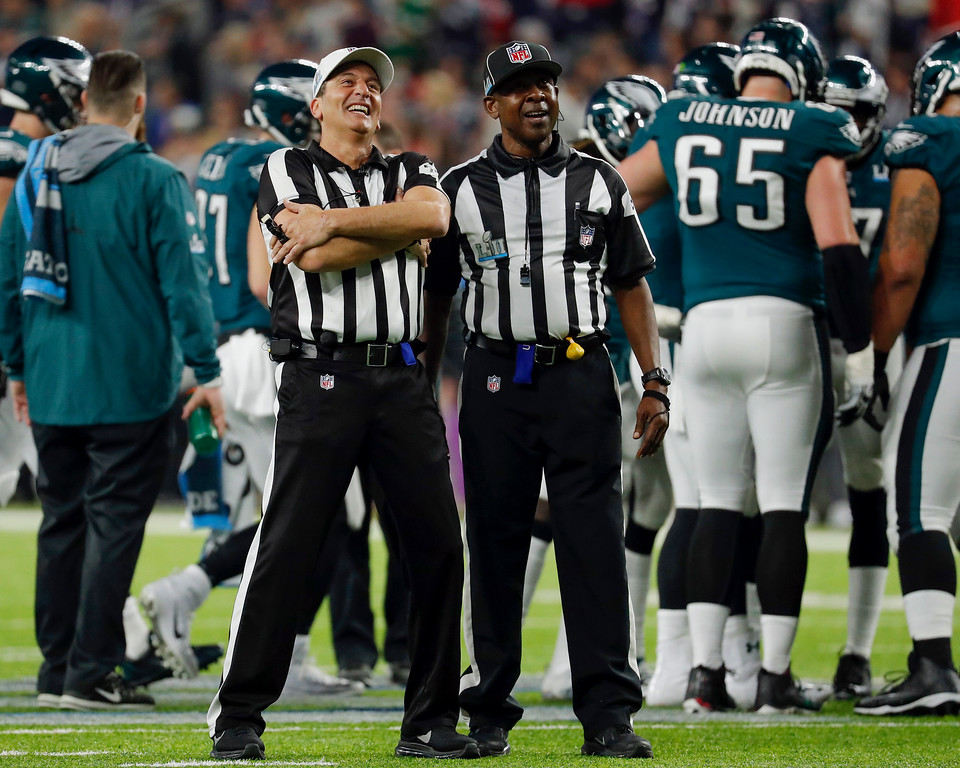. Officials laugh as they watch commercials on the scoreboard during the second half of the NFL Super Bowl 52 football game between the Philadelphia Eagles and the New England Patriots, Sunday, Feb. 4, 2018, in Minneapolis. (AP Photo/Charlie Neibergall)