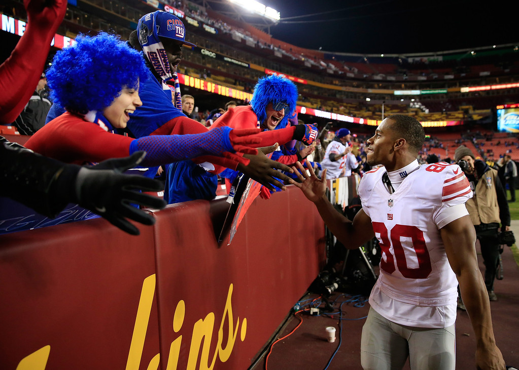 . LANDOVER, MD - DECEMBER 01: Wide receiver Victor Cruz #80 of the New York Giants celebrates with fans following the Giants 24-17 win over the Washington Redskins at FedExField on December 1, 2013 in Landover, Maryland.  (Photo by Rob Carr/Getty Images)