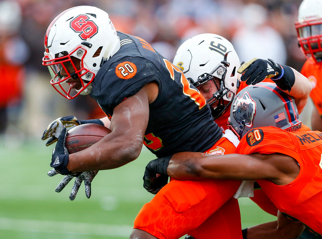 . South squad running back Matt Dayes of North Carolina State (20) carries the ball as North squad inside linebacker Connor Harris of Lindenwood (16) and safety Obi Melifonwu of Connecticut (20) tackle him during the second half of the Senior Bowl NCAA college football game, Saturday, Jan. 28, 2017, at Ladd-Peebles Stadium in Mobile, Ala. (AP Photo/Butch Dill)