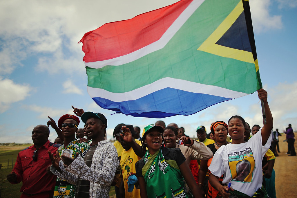 . People sing near the former South African President Nelson Mandela\'s home during his state funeral on December 15, 2013 in Qunu, South Africa. Mr. Mandela passed away on the evening of December 5, 2013 at his home in Houghton at the age of 95. Mandela became South Africa\'s first black president in 1994 after spending 27 years in jail for his activism against apartheid in a racially-divided South Africa.  (Photo by Dan Kitwood/Getty Images)