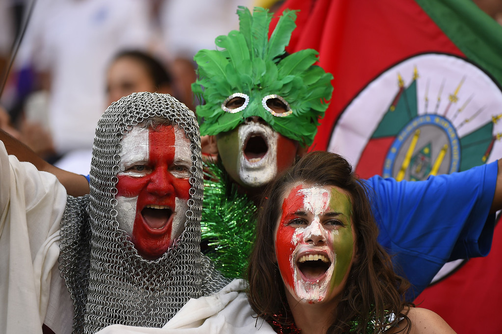 . An England fan (L) with his face painted in the colours of his national flag and wearing a chain mail costume cheers next to an Italian fan prior to a Group D football match between England and Italy at the Amazonia Arena in Manaus during the 2014 FIFA World Cup on June 14, 2014.  FABRICE COFFRINI/AFP/Getty Images
