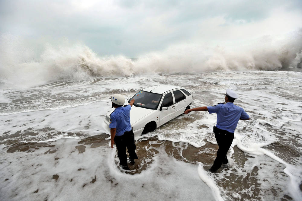 . This picture taken on August 28, 2012, shows police trying to help remove a car surrounded by water after its owner parked it on the bank to watch waves brought on by Typhoon Bolaven in Qingdao, in northeast China\'s Shandong province. Typhoon Bolaven -- the strongest storm to hit South Korea for almost a decade -- left a trail of death and damage in southwestern and south-central regions of the Korean peninsula on August 28, and crossed into China early on August 29.     AFP PHOTOSTR/AFP/Getty Images