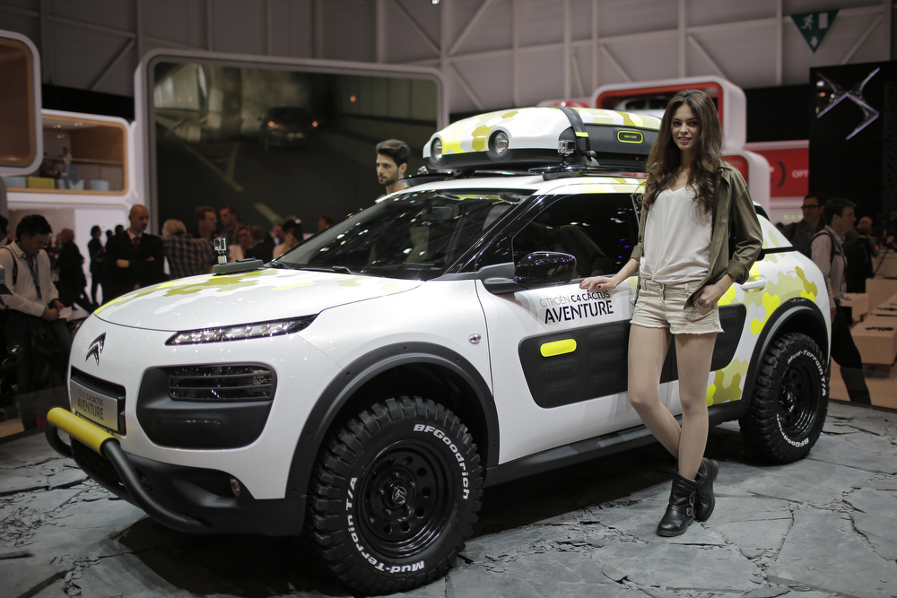 . A model poses in front of the new Citroen C4 Cactus during the media day of the 84th Geneva International Motor Show, Switzerland, Tuesday, March 4, 2014. The Motor Show will open its gates to the public from March 6 to 16. (AP Photo/Laurent Cipriani)
