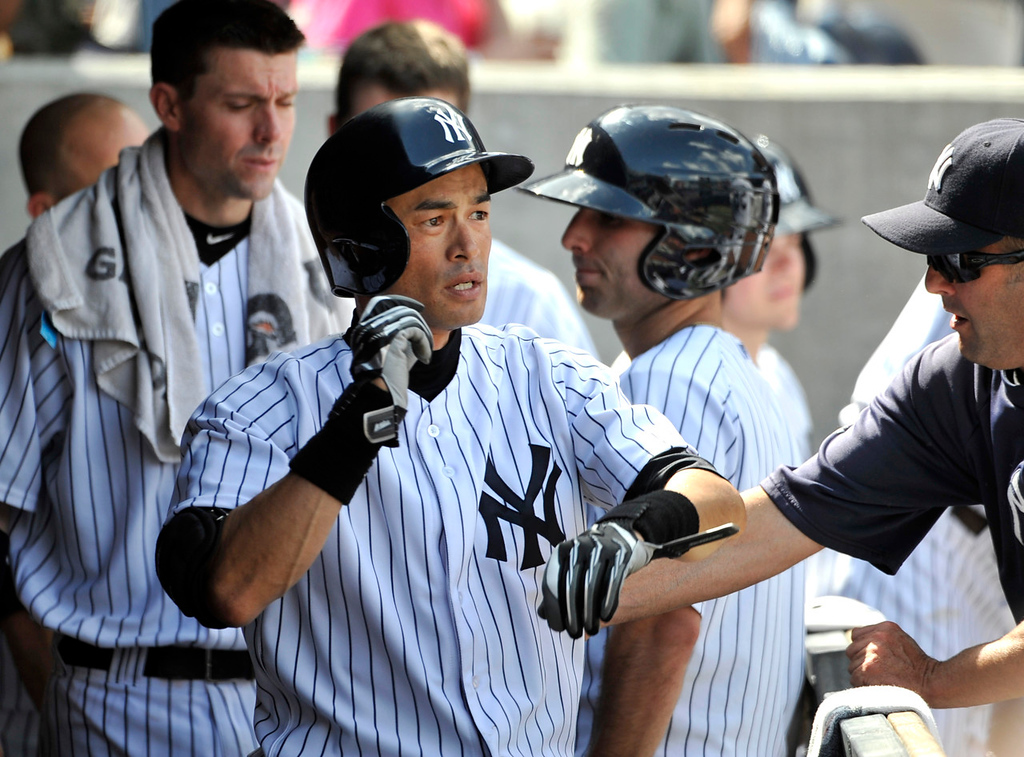 . New York\'s Ichiro Suzuki is greeted in the dugout after he his solo home run hit off  Twins relief pitcher Caleb Thielbar in the seventh inning. (AP Photo/Kathy Kmonicek)