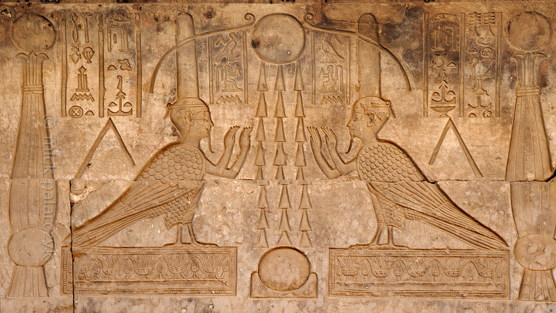 """[EGYPT 29618] 'Souls of Osiris at Dendera.'  Two images of the soul (ba) of Osiris in the form of a human headed bird decorate the court of the eastern Osiris chapels on the roof of the Hathor Temple at Dendera. The heads are topped by absurdly big """"perfume cones"""". The birds are placed on either side of three sun rays which connect a sun up in the sky and another one which is sitting on the horizon. This part of the Dendera Temple was built during the later Ptolemaic period (first century BC). Photo Mick Palarczyk."""