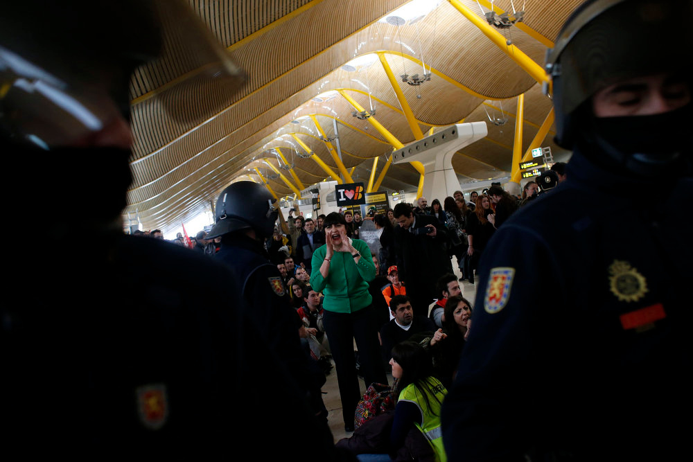 Description of . An Iberia airline worker shouts slogans at Spanish riot police officers during a protest at Madrid's Barajas airport February 18, 2013. Striking union workers clashed with police at the airport on Monday on the first day of a week-long strike over more than 3,800 pending job cuts at Spain's flagship airline Iberia. REUTERS/Susana Vera