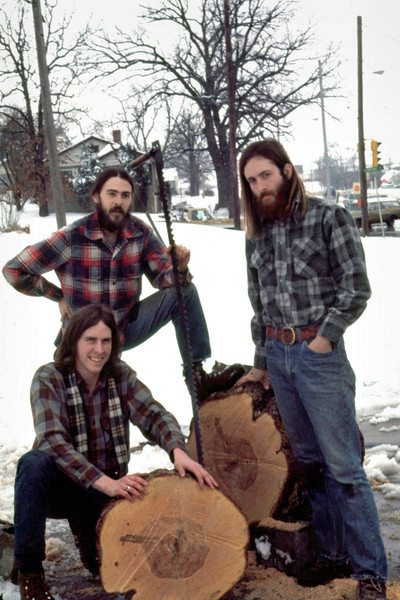 Tim, Gary and Kent, triumphant over a large oak log with a cross-cut saw. March 1975