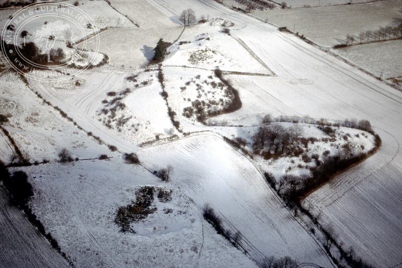 Farmland west of Ravlunda church - with plantations, buildings and prehistoric remains (20 February, 1988). | LH.0205