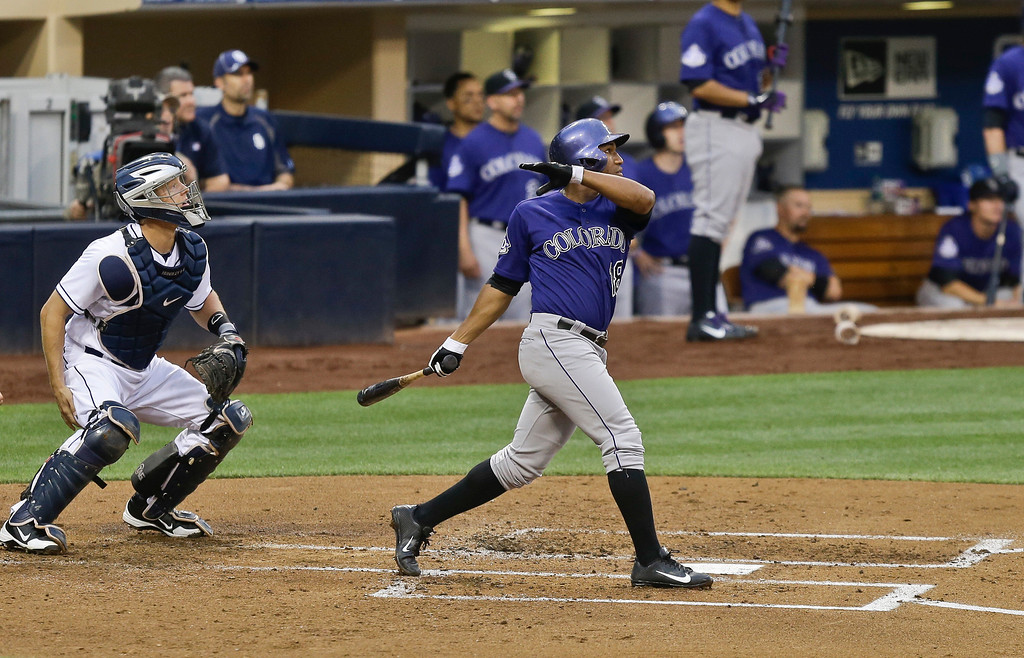 . Colorado Rockies\' Jonathan Herrera and San Diego Padres catcher Nick Hundley watch Herrera\'s long sacrifice fly to center filed that scored Todd Helton from third base in the second inning of a baseball game in San Diego, Wednesday, July 10, 2013. (AP Photo/Lenny Ignelzi)