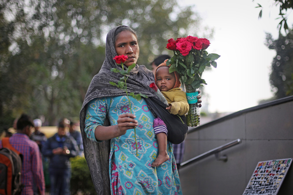 . An Indian street vendor holds a baby as she sells roses outside a metro station on Valentine\'s Day in New Delhi, India, Tuesday, Feb. 14, 2017. (AP Photo/Altaf Qadri)