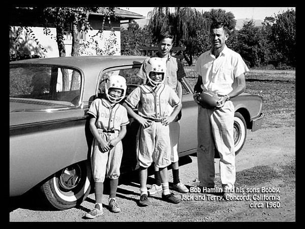 """Robert Hamlin with his sons Bobby, Jack and Terry Hamlin, in about 1960 in Concord, California. Jack and Terry are wearing """"Concord"""" baseball uniforms with football helmets."""
