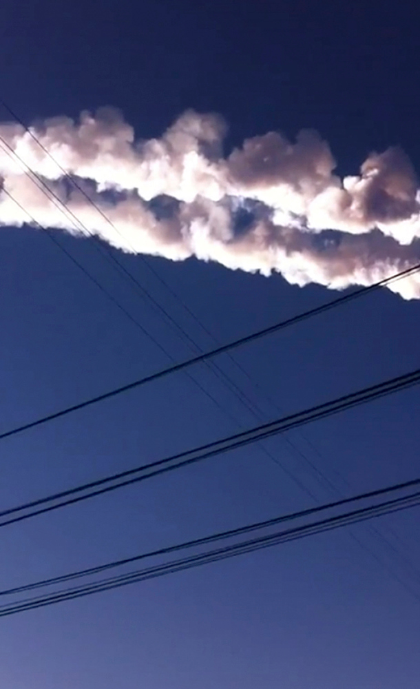 . In this photo taken with a mobile phone camera, a meteorite contrail is seen in Chelyabinsk region on Friday, Feb. 15, 2013. A meteor streaked across the sky of Russiaís Ural Mountains on Friday morning, causing sharp explosions and reportedly injuring around 100 people, including many hurt by broken glass. (AP Photo/Sergey Hametov)