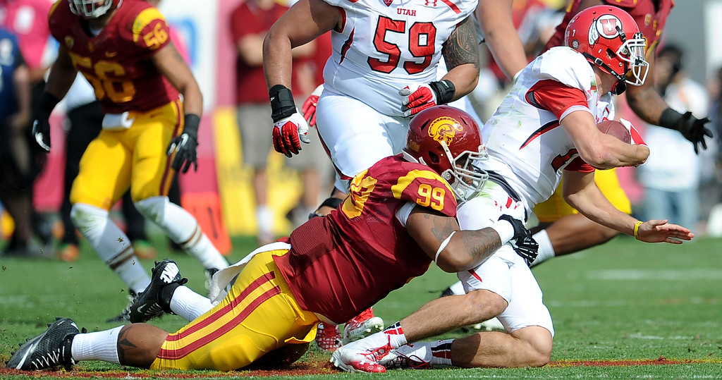 . Southern California defensive tackle Antwaun Woods (99) sacks Utah quarterback Travis Wilson (7) during the first half of an NCAA college football game in the Los Angeles Memorial Coliseum in Los Angeles, on Saturday, Oct. 26, 2013.  (Photo by Keith Birmingham/Pasadena Star-News)