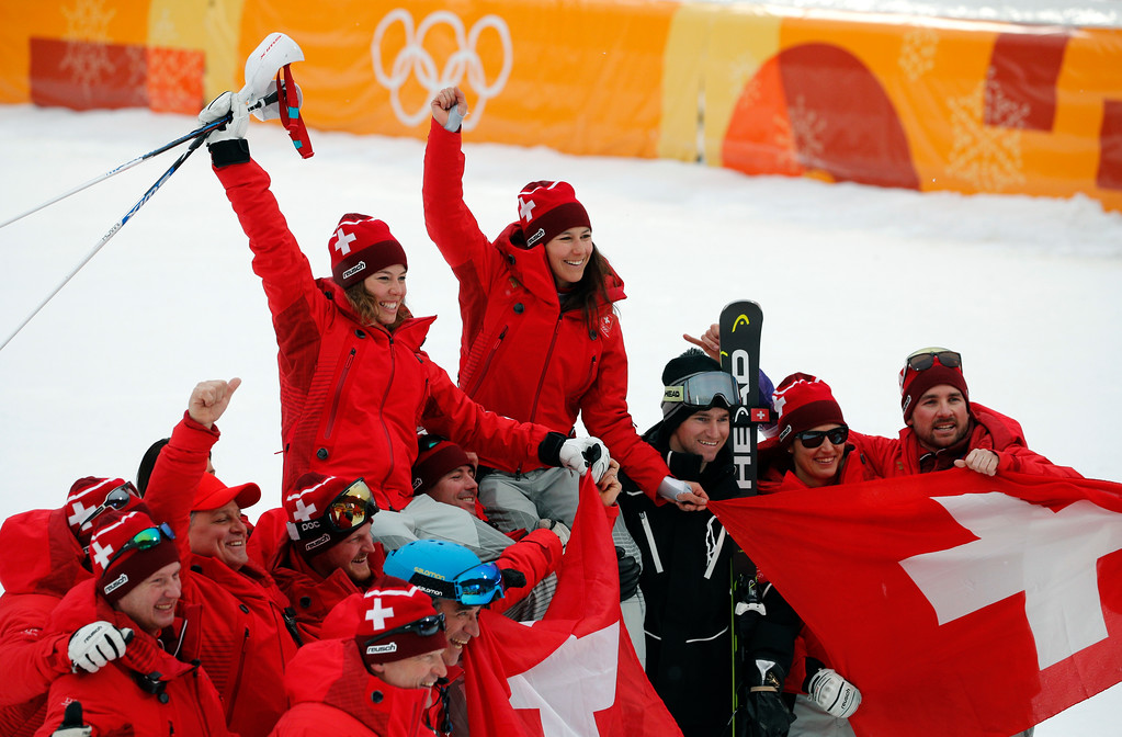 . Switzerland\'s Michelle Gisin, left, gold, and Switzerland\'s Wendy Holdener, bronze, are hoisted aloft by team members after the flower ceremony for the women\'s combined slalom at the 2018 Winter Olympics in Jeongseon, South Korea, Thursday, Feb. 22, 2018. (AP Photo/Christophe Ena)