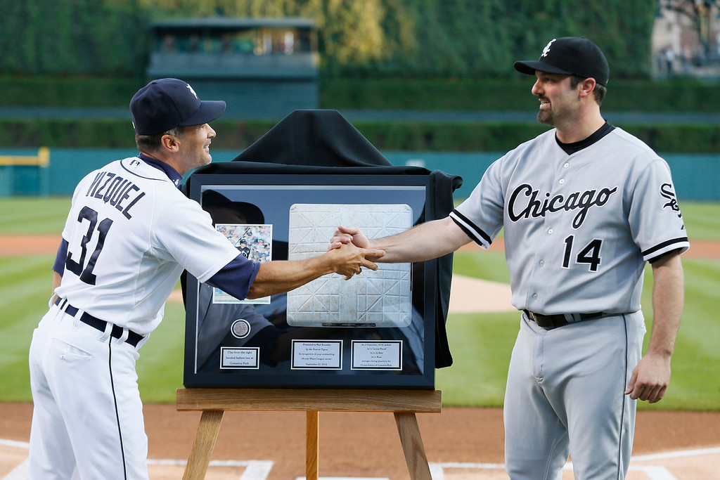 . Chicago White Sox designated hitter Paul Konerko (14)  shakes hands with Detroit Tigers first base coach Omar Vizquel (31) while being honored before a baseball game in Detroit Tuesday, Sept. 23, 2014. Konerko will be retiring after the season. (AP Photo/Paul Sancya)