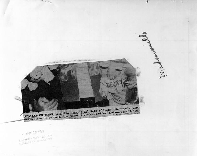 """Japanese orphans, good Americans, were not forgotten by Santa.  At a Fraternal Order of Eagles (Hollywood) party, Joe Mari and Sumi Kukasowa met St. Nick.""--caption on photograph"