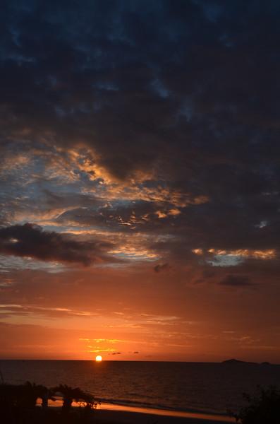 Crimson Tropical sunrise seascape with pink tinged dark nimbostratus cloud. Huay Yang, Thailand.