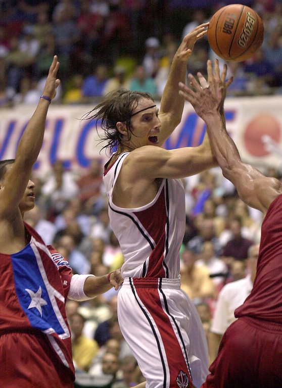 . Canada\'s Steve Nash, center, of the Dallas Mavericks, drives the ball between Puerto Rico\'s Roberto Hatton, left, and Jose Ortiz during the third-place game of the FIBA Americas Olympic Qualifying Tournament at the Roberto Clemente Coliseum in San Juan, Puerto Rico, Sunday, Aug. 31, 2003. (AP Photo/Andres Leighton)